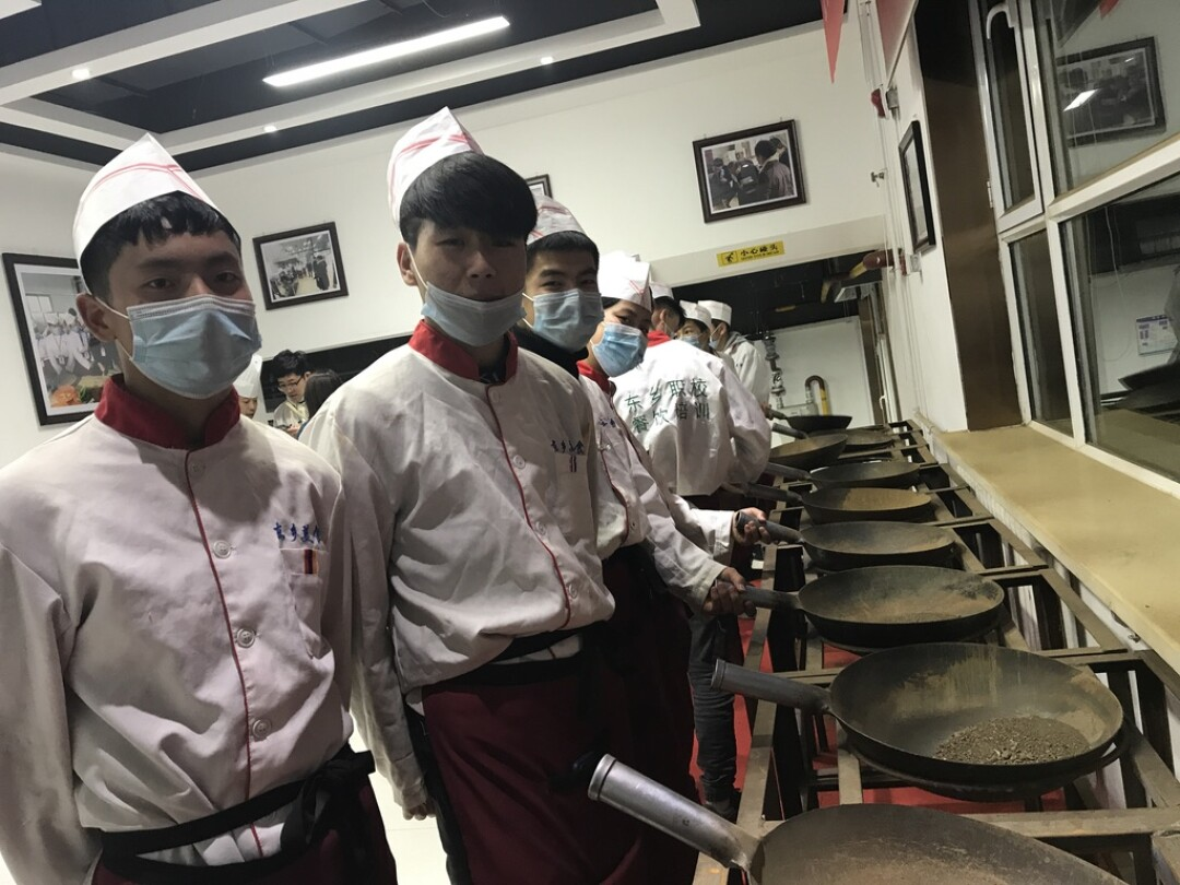 Dongxiang teenagers practice flipping woks at a vocational school near Linxia.