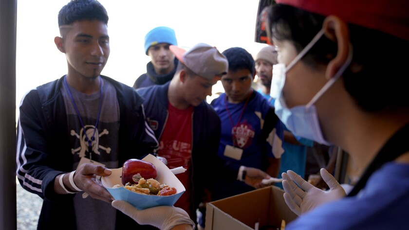 A volunteer at El Barretal migrant shelter in Tijuana helps pass out the hot meals consisting of a t