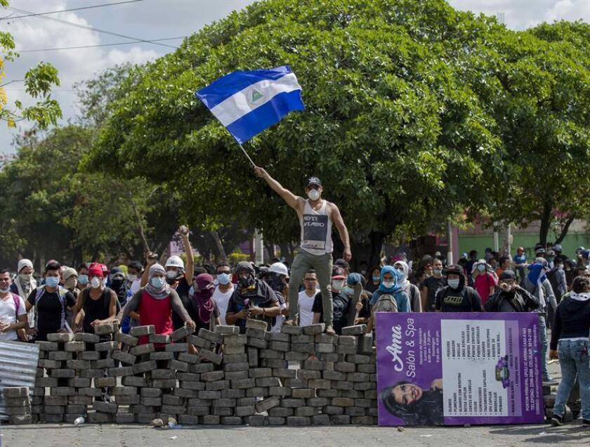 Un joven levanta una bandera de Nicaragua sobre una barricada de adoquines durante una protesta en Managua (Nicaragua). EFE