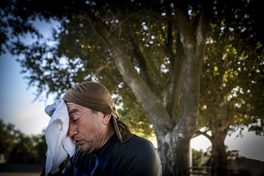 Mountain biker Guillermo Salazar of Reseda wipes sweat from his forehead while taking a break from riding amid temperatures in the 90s at San Vicente Mountain Park in Los Angeles.