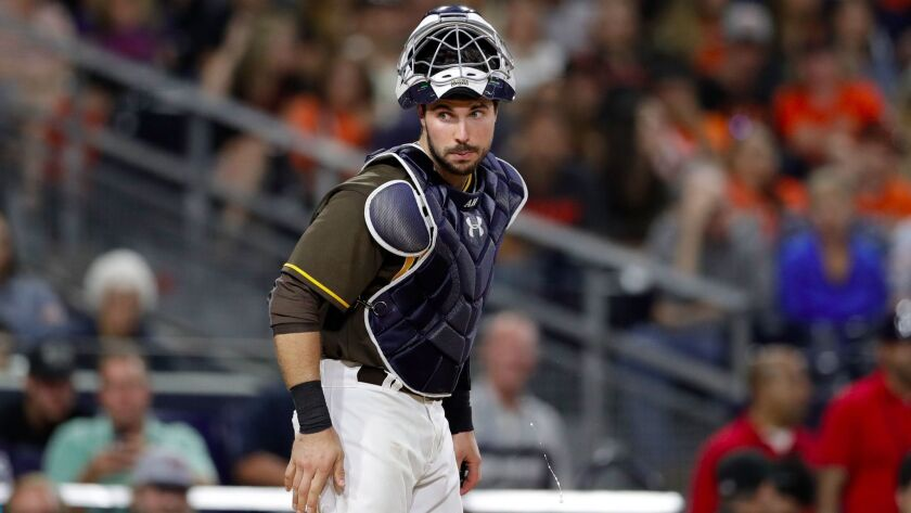 San Diego Padres catcher Austin Hedges looks on after being hit by a ball in the facemask during the