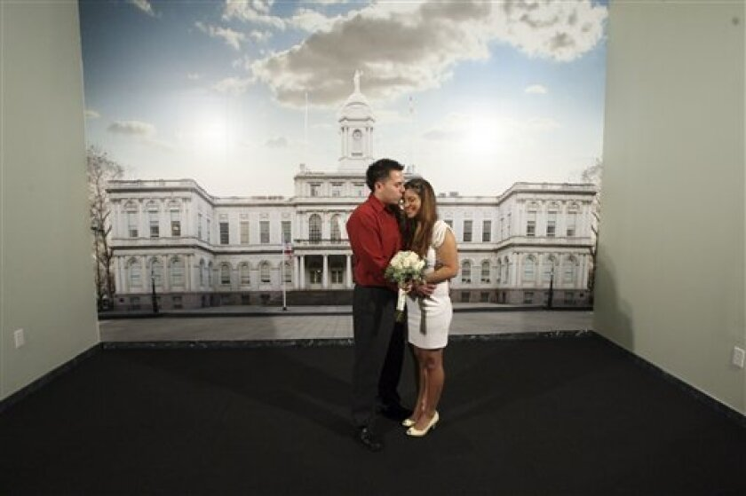 Carlos Sanchez kisses his bride Jennifer Avilla at the photo wall after getting married during the press preview of New York's new Office of the City Clerk/Marriage Bureau, Wednesday, Jan. 7, 2009.  New York has given its marriage bureau a drastic makeover in hopes of making it a Las Vegas-style we