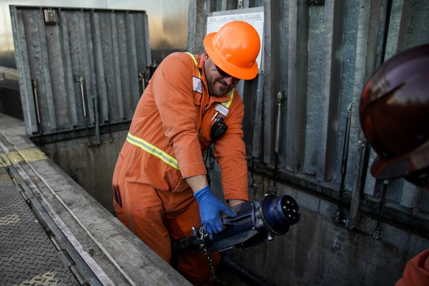 Mechanics prepare to connect a container ship to the TraPac terminal power grid.