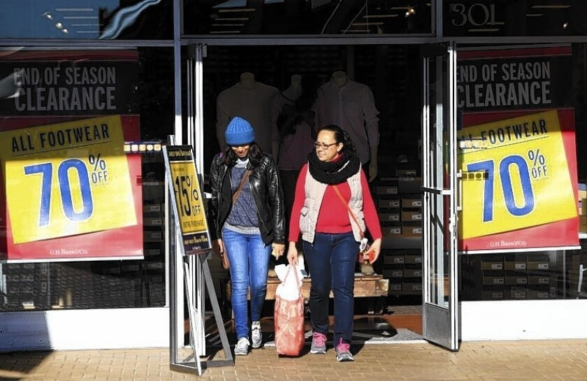 Shoppers exit the Bass store at the Citadel Outlets in Los Angeles where the retailer was offering up to 70% off on Christmas Eve.