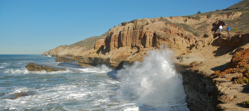 Waves batter the cliffs while two hikers pass at Cabrillo National Monument in Point Loma. Photo tak