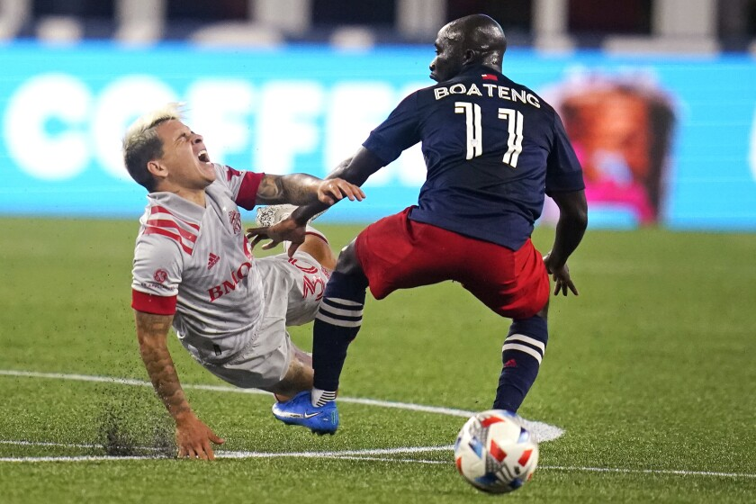 Toronto FC midfielder Yeferson Soteldo, left, yells as he is tripped by New England Revolution midfielder Ema Boateng (11) during the second half of an MLS soccer match, Wednesday, July 7, 2021, in Foxborough, Mass. Toronto won 3-2. (AP Photo/Charles Krupa)