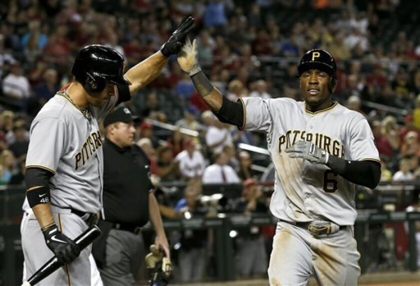 Pittsburgh Pirates' Starling Marte (6) gets a high-five from teammate Garrett Jones after Marte scored a run against the Arizona Diamondbacks during the first inning in a baseball game, on Monday, April 8, 2013. (AP Photo/Ross D. Franklin)