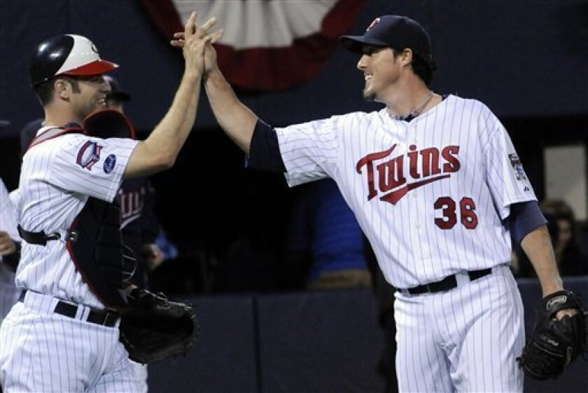 Minnesota Twins catcher Joe Mauer, left, and pitcher Joe Nathan celebrate their 10-7 win over the Kansas City Royals, Friday, Oct. 2, 2009, in Minneapolis. Nathan set a Twins all-time single season record with his 46th save. (AP Photo/Jim Mone)
