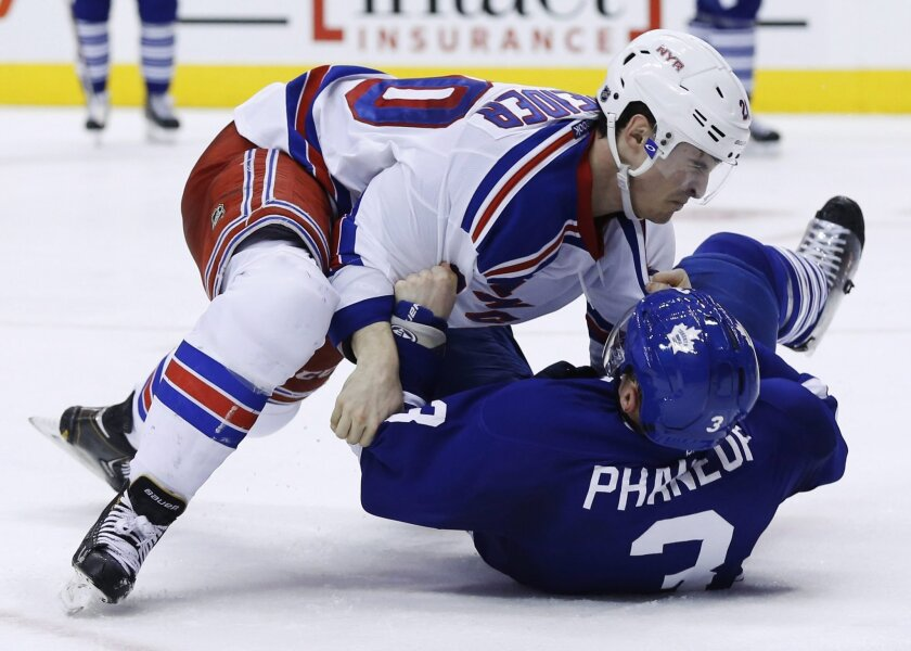 New York Rangers' Chris Kreider, left, takes Toronto Maple Leafs' Dion Phaneuf to the ice in a fight during the third period of an NHL hockey game in Toronto, Saturday, Jan. 4, 2014. (AP Photo/The Canadian Press, Mark Blinch)