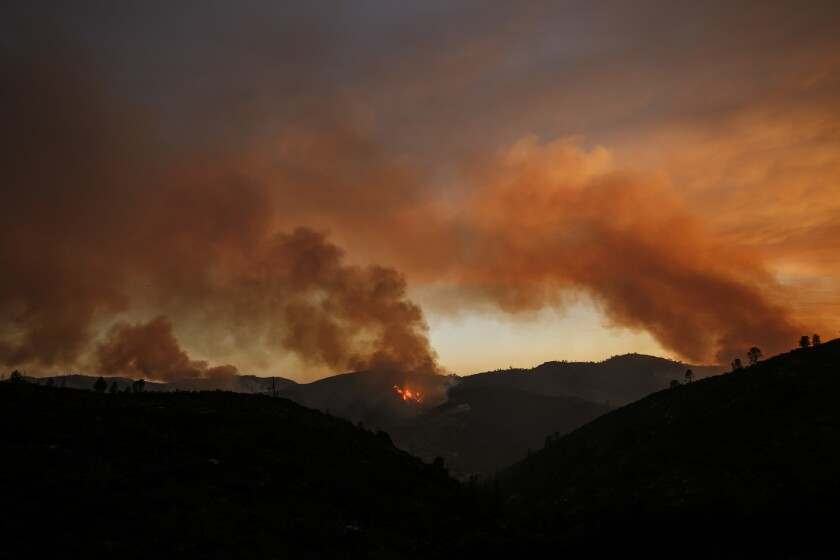 Plumes of smoke rises as the northern front of the Detwiler wildfire burns outside of Coulterville, Calif.