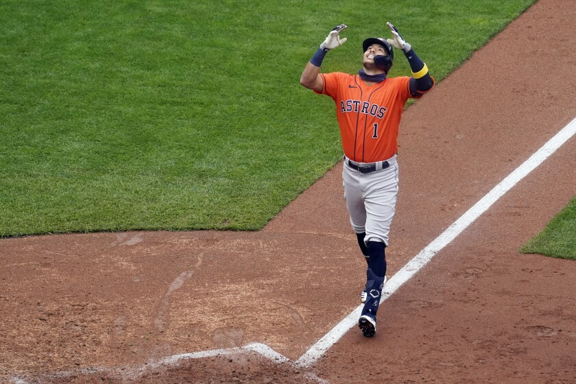 Houston Astros' Carlos Correa celebrates his go-ahead solo home run off Minnesota Twins relief pitcher Cody Stashak in the seventh inning in Game 2 to clinch the American League wild-card baseball series, Wednesday, Sept. 30, 2020, in Minneapolis. The Astros won 3-1 to win the three-game series. (AP Photo/Jim Mone)