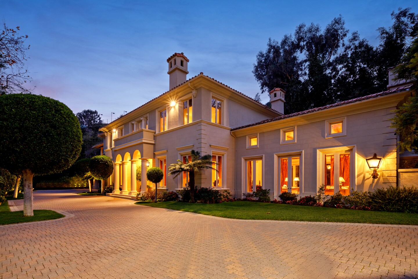 """The Bel-Air estate of late automobile titan Lee Iacocca sold for $19.5 million after listing for sale in January at about $26 million. The Iacocca family were the original owners of the property, which sits on more than an acre with a swimming pool, gardens and a tennis court. Among features of the Italianate-vibe house are five fireplaces, a foyer with arched ceilings and a grand living room. French doors open onto a stone pavilion. The estate on Chalon Road entered escrow amid the pandemic in March and sold a month later to Lilly Halichi and Dara Mir, who appear on""""Shahs of Sunset."""""""