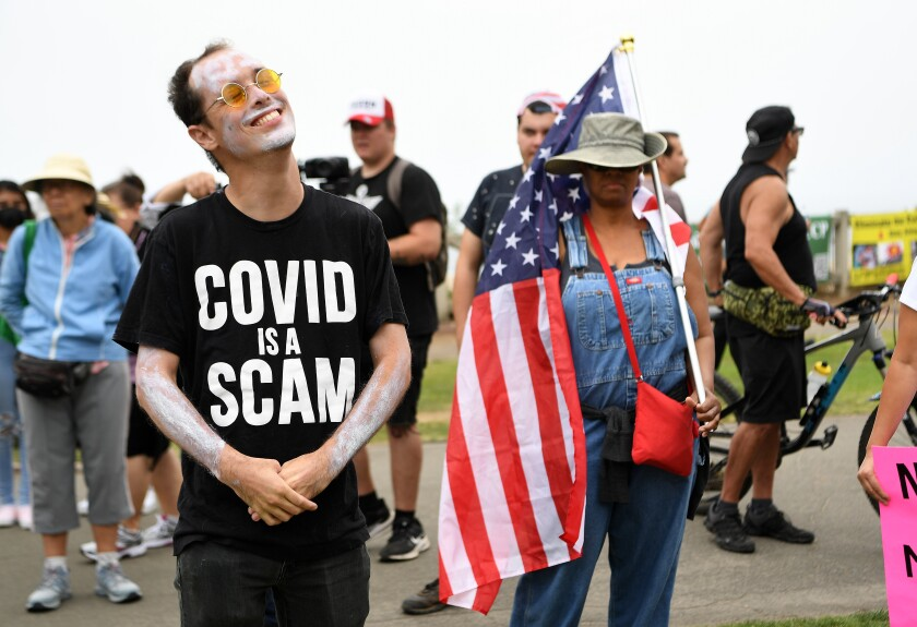 A man in a shirt that says COVID is a scam