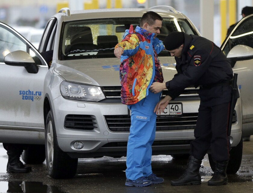 NBC executives said Thursday that they are comfortable with security efforts for the Winter Olympics. Above, a Russian police officer searches a driver as his vehicle is also screened at an entrance to the Sochi 2014 Olympic Winter Games park, Jan. 23, 2014, in Sochi, Russia.