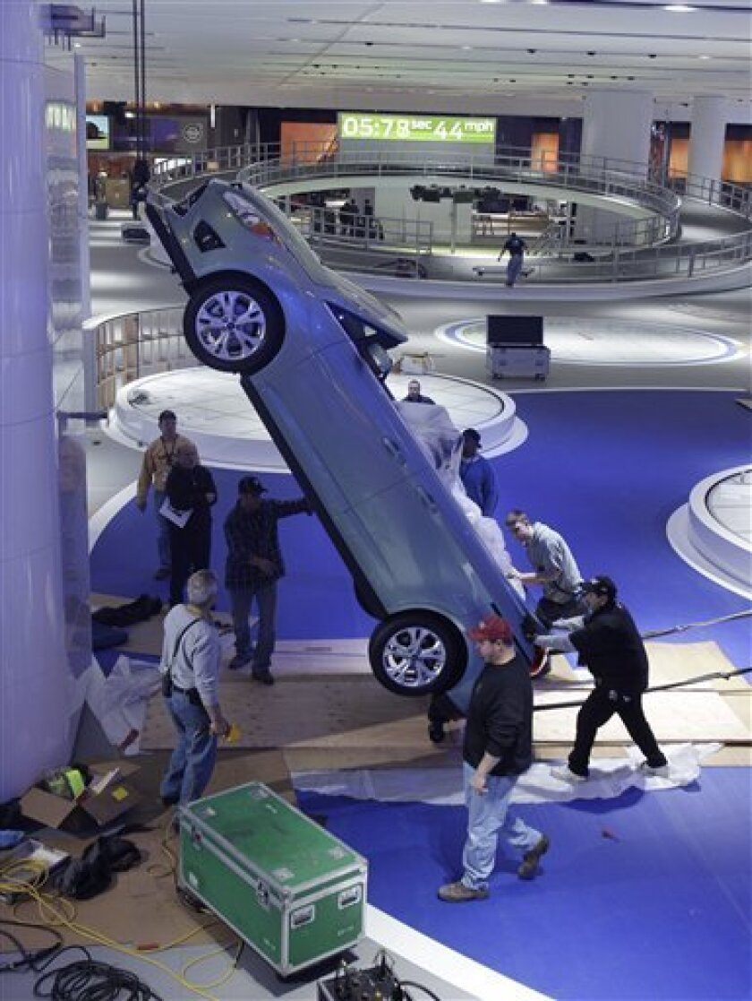 Construction workers lift a Ford C-Max model to a vertical display at the Ford exhibit at the North American International Auto Show in Detroit, Wednesday, Jan. 5, 2011. Automakers are spending more money on glitzy, state-of-the-art exhibits at the North American International Auto Show in Detroit. The show's media days begin Monday, Jan. 10. (AP Photo/Carlos Osorio)