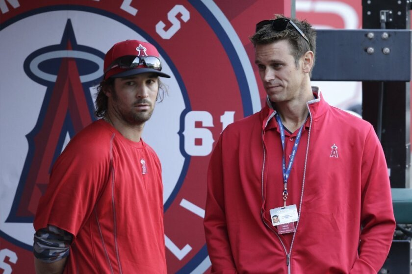 Angels pitcher C.J. Wilson talks with General Manager Jerry Dipoto before a game against the Kansas City Royals on April 11.