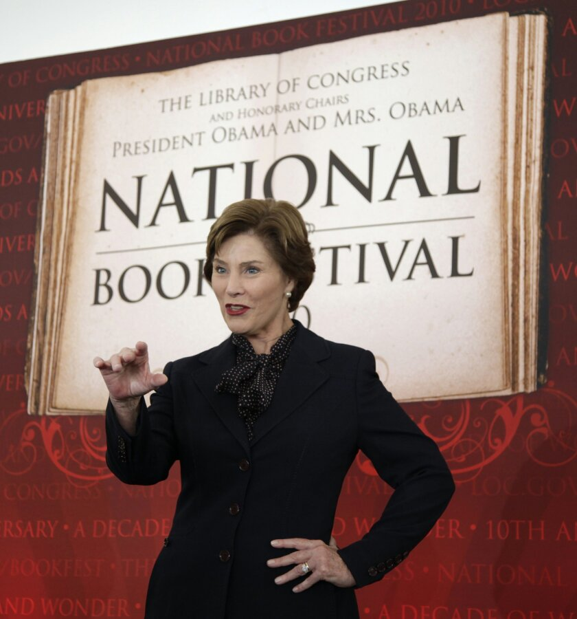 FILE - This Sept. 25, 2010 file photo shows former first lady Laura Bush speaking at the 10th annual National Book Festival, organized and sponsored by the Library of Congress, on the National Mall in Washington. After a decade on the National Mall, the National Book Festival is moving to a new location this year due to new rules and costs associated with holding a large event on the promenade between the Capitol and Lincoln Memorial. The Library of Congress announced Wednesday that the popular literary event will move this year to the Washington Convention Center and will add a movie screening and cinema programs in the evening. This year's festival is scheduled for Aug. 30. (AP Photo/Carolyn Kaster, File)