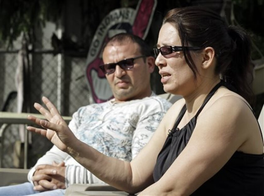 Elida Caraballo, right, talks about the abuse her late sister, Grimilda Figueroa, suffered at the hands of her common law husband, Ariel Castro, during an interview with her husband, Frank, at their home in Cleveland Thursday, May 9, 2013. Castro has been charged with kidnapping and rape for holding three women captive for a decade in his Cleveland home. (AP Photo/Mark Duncan)
