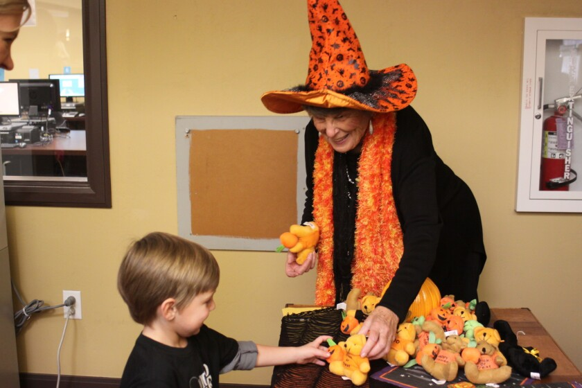 Witchy-poo hands a young library patron a treat at last year's Spooky Storytime.