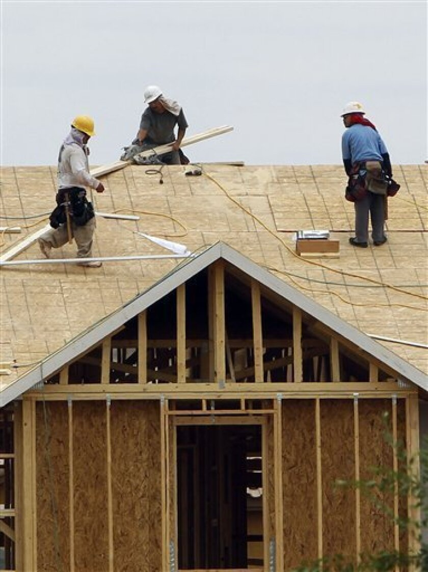 In this June 28, 2011 photo, construction workers spend time on the roof of a house in the Estates at Cameron Ranch, in Gilbert, Ariz. Builders began work on more home-remodeling projects in May. But the increase barely lifted construction spending above its lowest level in more than a decade, a sign that the industry is too weak to provide a boost to the economy. (AP Photo/Ross D. Franklin)