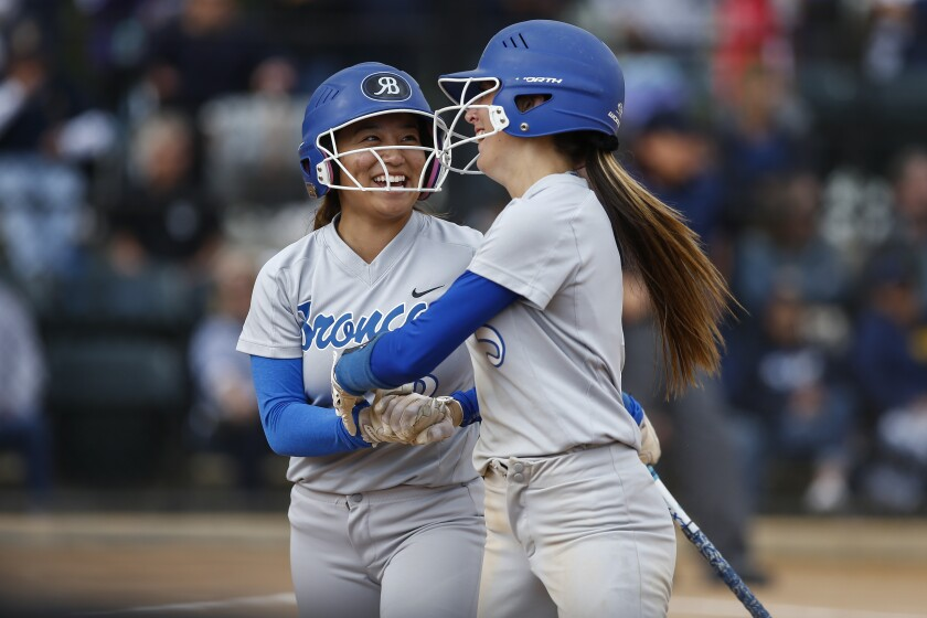 Rancho Bernardo's Mia Rushton (5), right, is celebrated by Christina Sugimoto, left, after Rushton stole home on a play in the fourth inning against Bonita Vista.