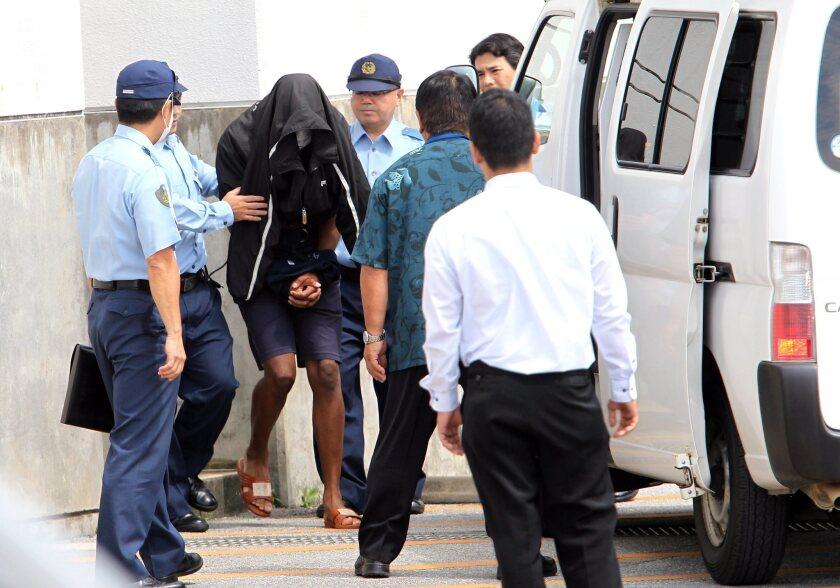 Former U.S. Marine Kenneth Shinzato is escorted by police officers from Uruma Police Station in Uruma, Okinawa, southwestern Japan on Friday.
