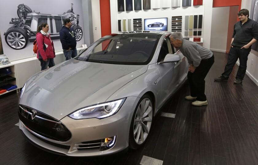 Customers look at a Tesla Model S in a company showroom in Cincinnati.