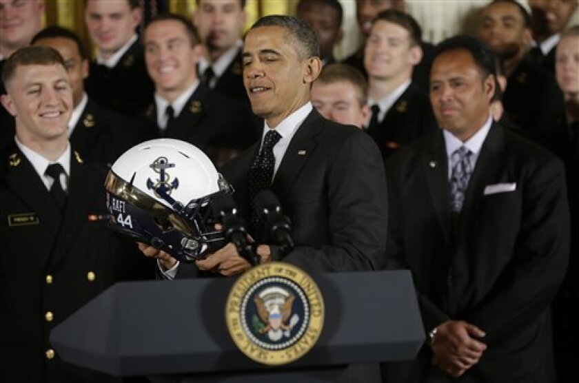 "President Barack Obama holds a Navy football team helmet in the East Room of the White House in Washington, Friday, April 12, 2013, after presenting the Commander-in-Chief Trophy to the United States Naval Academy football team. The helmet bears a ""44"" sticker for President Obama being the 44th pre"
