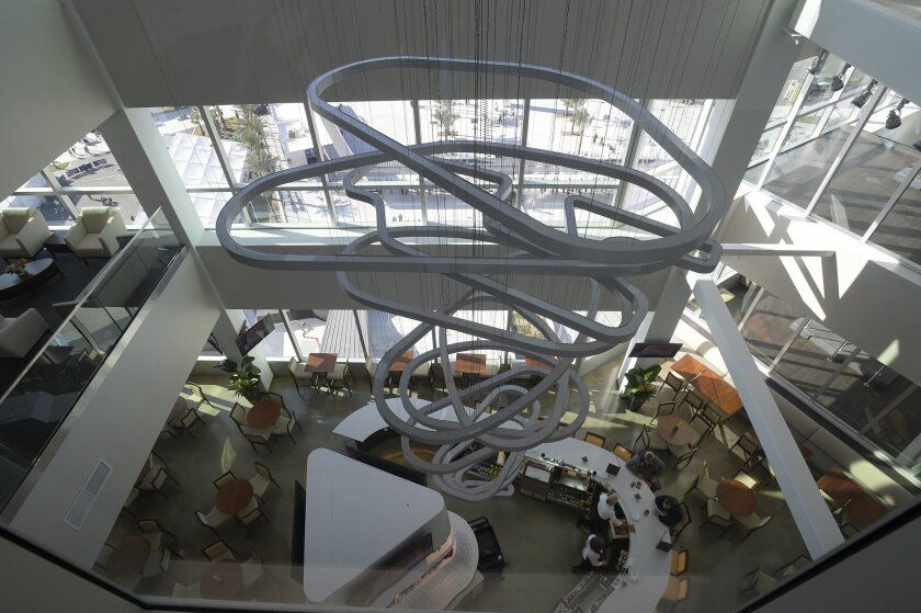 """In this Feb. 13, 2016,  photo, a sculpture hangs over a bar at Daytona International Speedway in Daytona Beach, Fla. The project was such a massive undertaking that architects had to account for the curvature of the Earth. It also got its own nickname, """"Daytona Rising."""" Now, the $400 million renova"""