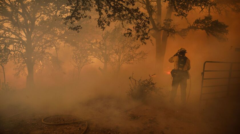 LAKEPORT, CALIF. -- TUESDAY, JULY 31, 2018: A firefighter holds on to his helmet on as a gust of win