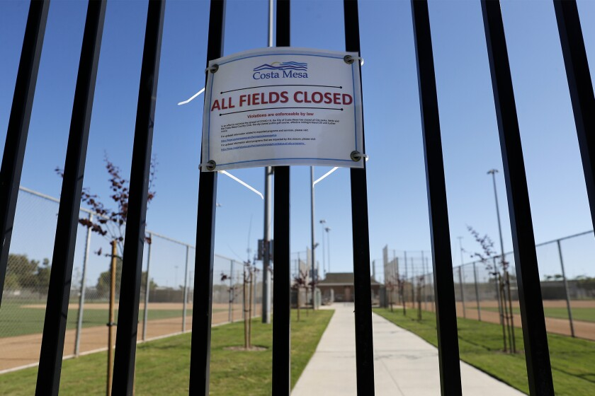 A closure notice is posted on the north gate at TeWinkle Athletic Complex in Costa Mesa on Saturday. Local PONY baseball leagues are sidelined by the coronavirus and are unsure if they will be able to resume play this season.
