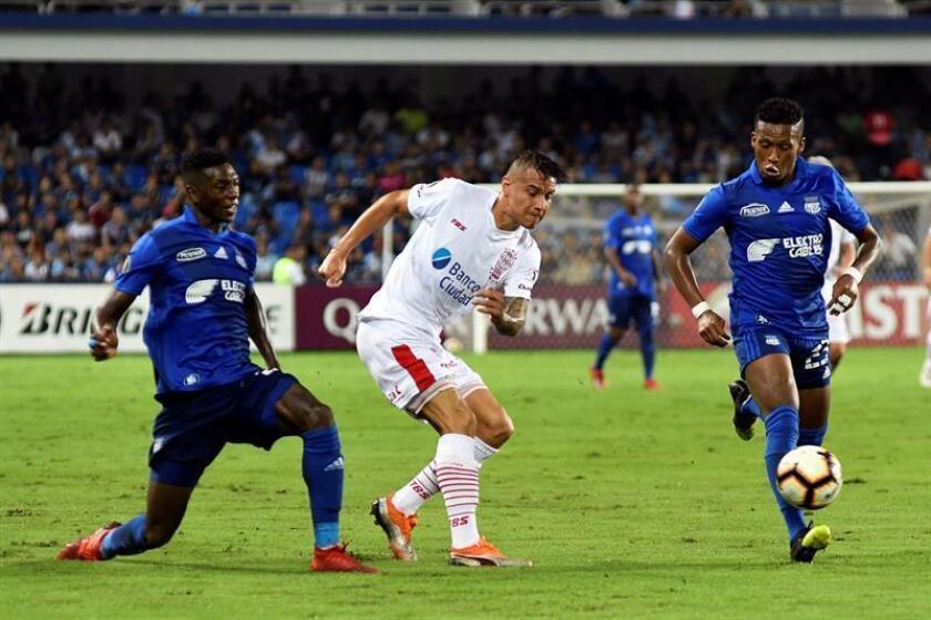 Los jugadores de Emelec Fernando guerrero (d) y Dixon Arroyo (i) disputan el balón con Carlos Auzqui (c) de Huracán durante un partido por el grupo B de la Copa Libertadores en el estadio George Capwell de Guayaquil (Ecuador). EFE