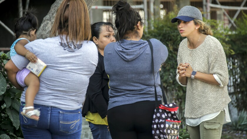 Owner of apartment complex Gelena Skya-Wasserman, right, talks a group of tenants who are picketing to block workers from sandblasting their courtyard.