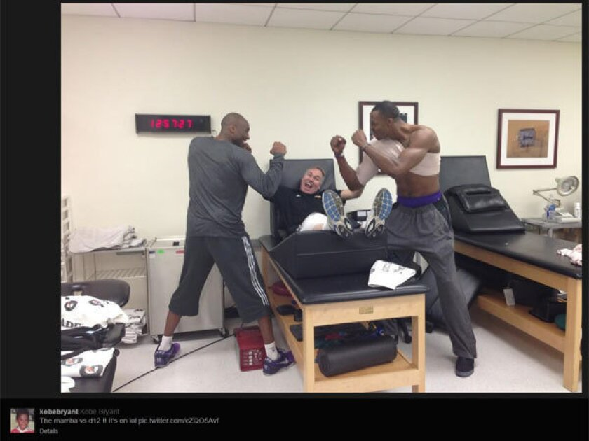 Kobe Bryant and Dwight Howard -- his injured shoulder heavily wrapped -- pretend to fight as Lakers Coach Mike D'Antoni plays peacemaker.