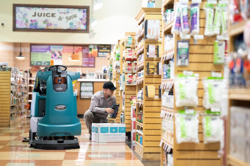 A Tennant Co. robotic floor scrubber powered by Brain Corp.'s BrainOS operating system maneuvers around a worker restocking shelves. Brain Corp. aims to become the Microsoft of the autonomous mobile robotics industry.