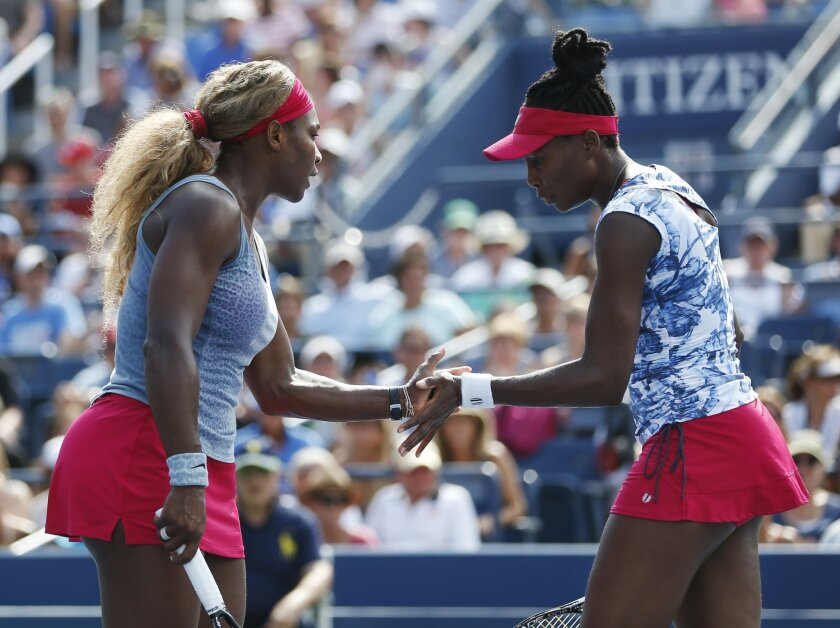 Serena, left, and Venus Williams slap hands between points against Garbine Muguruza and Carla Suarez Navarro, of Spain, during a doubles match at the 2014 U.S. Open tennis tournament, Sunday, Aug. 31, 2014, in New York. (AP Photo/Seth Wenig)