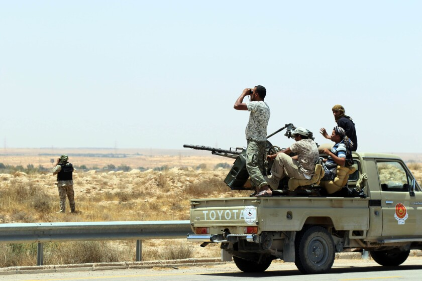 Forces loyal to Libya's U.N.-backed unity government sit on the back of an armored vehicle at the entrance to Surt as they advance to recapture the city from the Islamic State group jihadists on June 10.