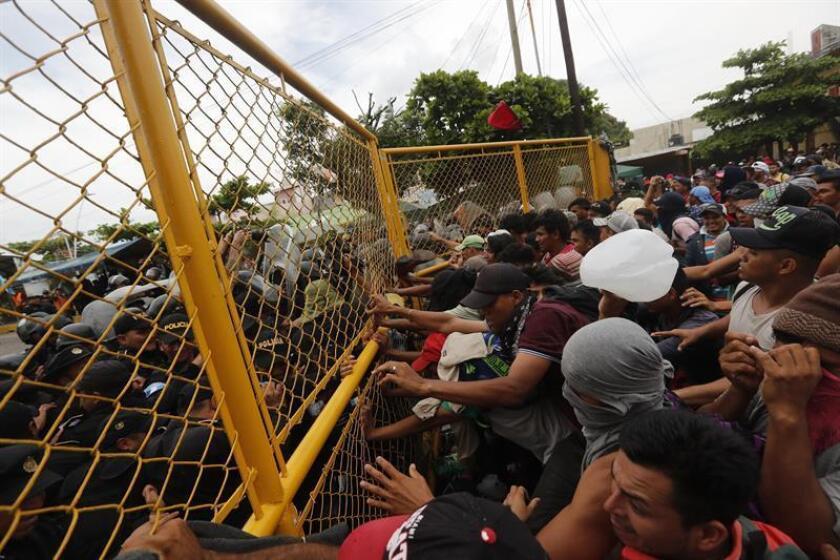 Cientos de migrantes centroamericanos que hacen parte de una segunda caravana rumbo a EE.UU intentan cruzar en el paso fronterizo entre México y Guatemala hoy, domingo 28 de octubre de 2018, en Tecún Umán (Guatemala). EFE