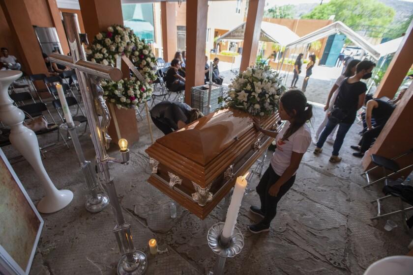 A mourner touches a casket.