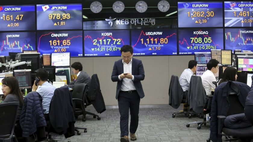 A currency trader watches his mobile phone at the foreign exchange dealing room of the KEB Hana Bank