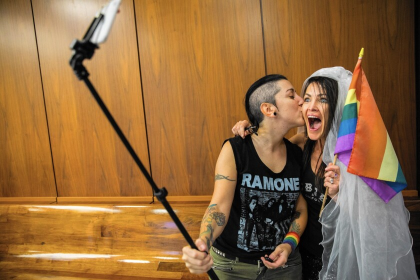Natalie Novoa, left, left, and Eddie Daniels take a selfie while waiting to be married at the L.A. County registrar's Beverly Hills office on Friday.