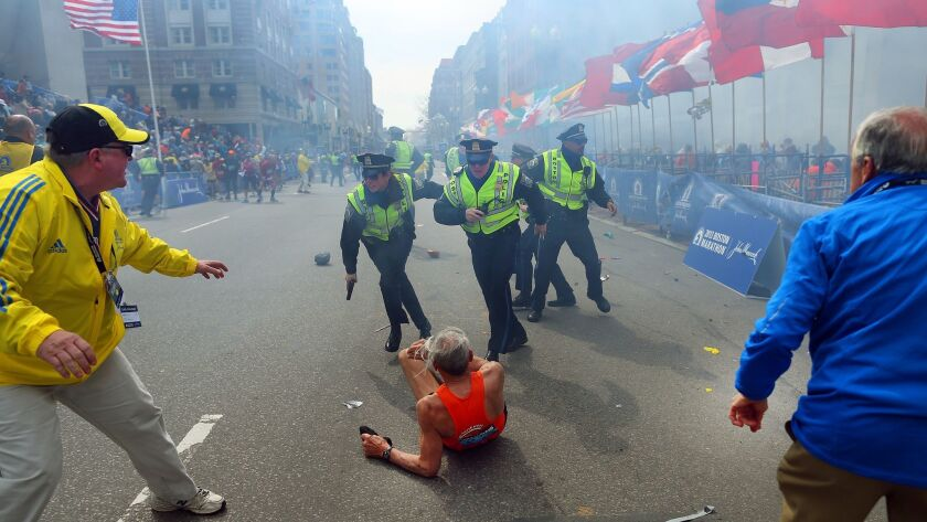 Police officers with their guns drawn hear a second explosion at the 2013 Boston Marathon. The first explosion knocked down a runner near the finish line.
