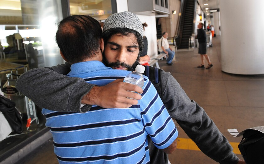 Rehan Motiwala hugs his father Rafiq after arriving at LAX.
