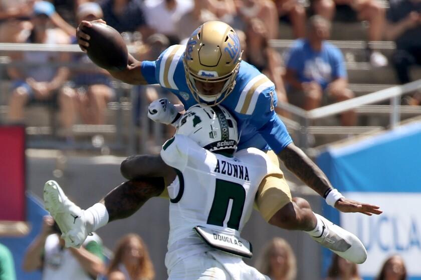 PASADENA, CALIF. - AUG. 28, 2021. UCLA quarterback Dorian Thompson-Robinson tries to hurdle.