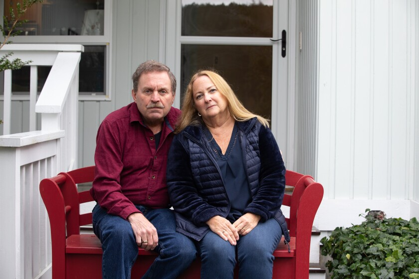 Jim Owen and Carolynn Comstock, singers in the Skagit Valley Chorale, sit outside their home in Anacortes, Wash.