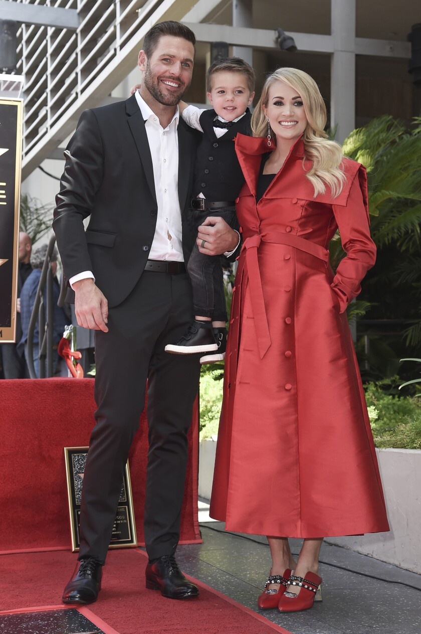"""FILE - In this Sept. 20, 2018 file photo, singer Carrie Underwood poses with her husband Mike Fisher, and their son Isaiah Michael Fisher as they attend a ceremony honoring Underwood with a star on the Hollywood Walk of Fame, in Los Angeles. Underwood's son provided the adorable vocals on """"Little Drummer Boy,"""" one of the 11 tracks on the country superstar's new Christmas album, """"My Gift,"""" out Friday, Sept. 25, 2020. (Photo by Richard Shotwell/Invision/AP, File)"""