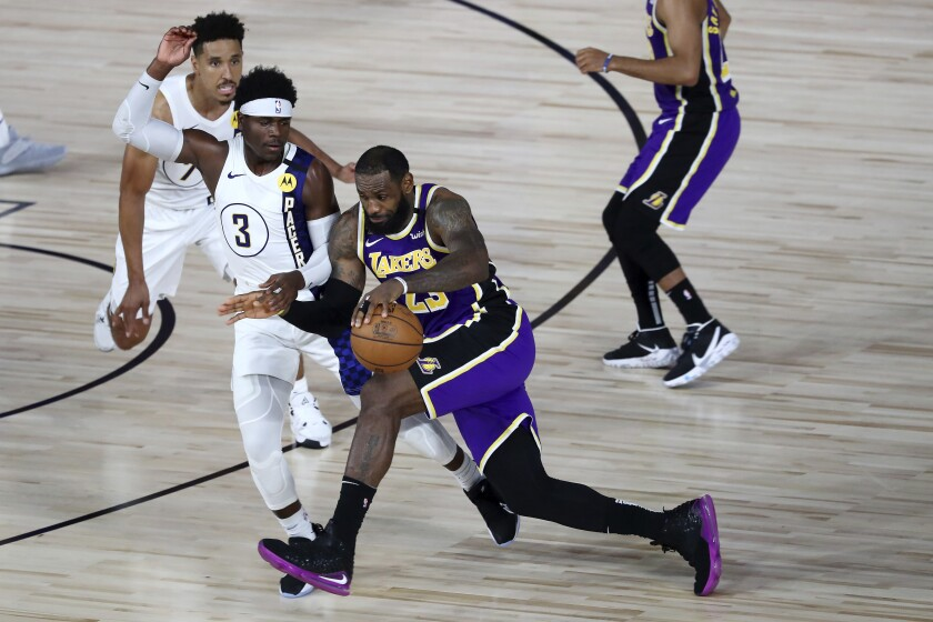 The Lakers' LeBron James drives against the Pacers' Aaron Holiday during the fourth quarter.
