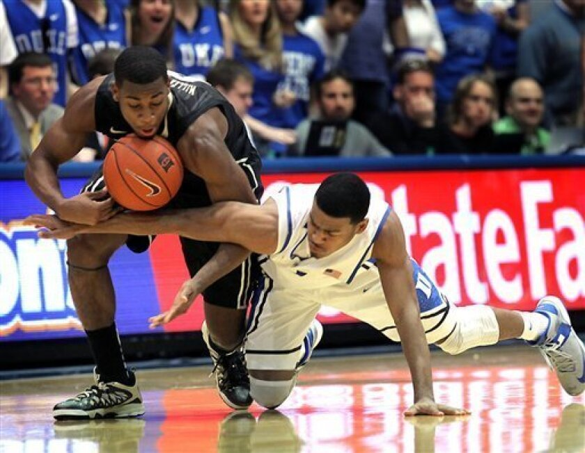 Duke's Quinn Cook, right, and Wake Forest's Codi Miller-McIntyre fight for a loose ball during the second half of an NCAA college basketball game in Durham, N.C., Saturday, Jan. 5, 2013. Duke won 80-62. (AP Photo/Ted Richardson)