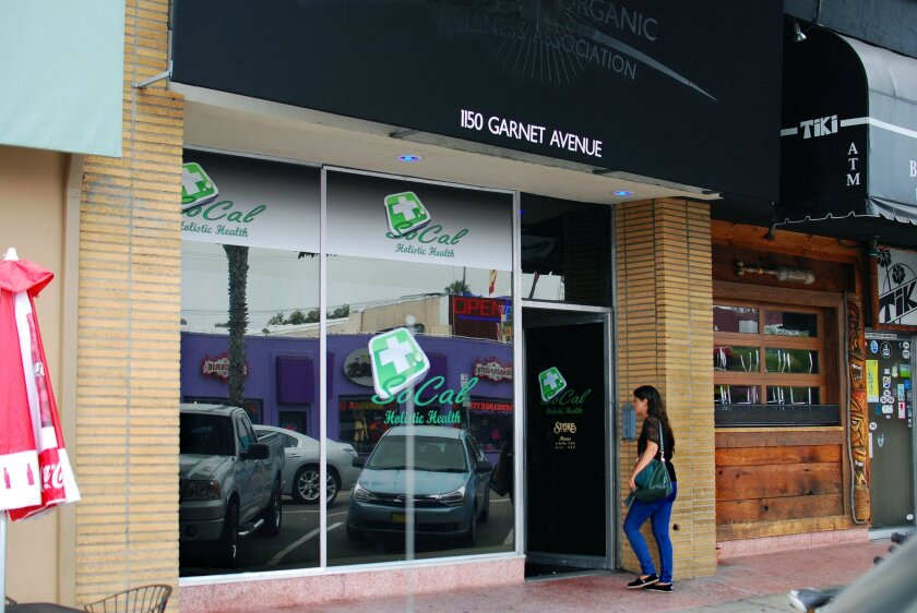 A woman enters So Cal Holistic Health, a medical marijuana dispensary in Pacific Beach. Dispensaries are operating illegally in the city of San Diego and most give little outward indication of what they sell.
