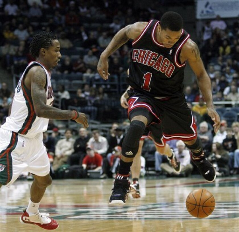 Milwaukee Bucks' Brandon Jennings knocks the ball away from Chicago Bulls' Derrick Rose (1) during the first half of an NBA basketball game Monday, Nov. 30, 2009, in Milwaukee. (AP Photo/Morry Gash)
